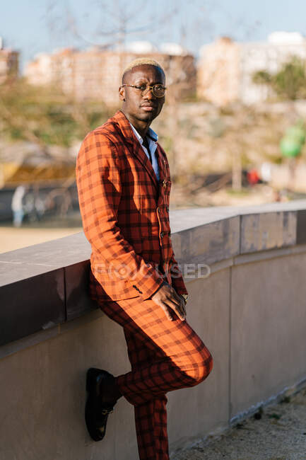 African American male in tartan outfit and eyeglasses looking at camera while standing with raised leg in town — Stock Photo
