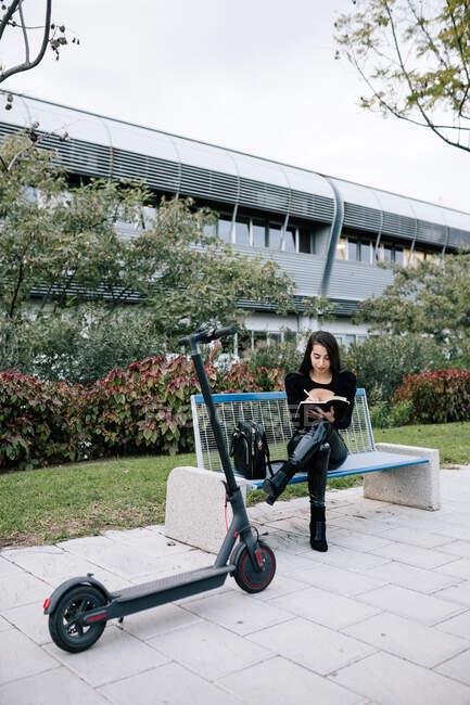 Зосереджений жіночий підприємець сидить на лавці біля сучасного електричного скутера і пише план у записнику під час віддаленого міського парку. — стокове фото