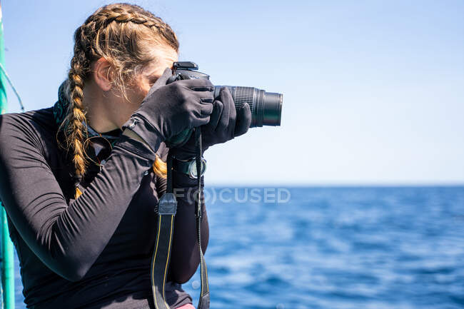 Side view of female traveler taking photo of sea on professional camera during trip — Stock Photo