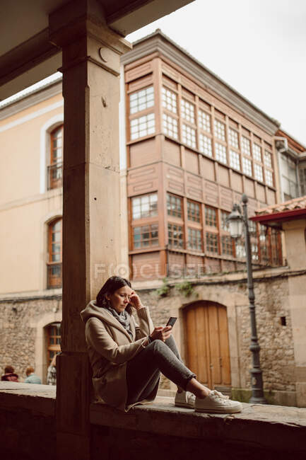 Side view of female in outerwear text messaging on cellphone while touching face in city — Stock Photo