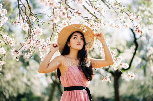 Peaceful ethnic female in straw hat and dress standing under blooming fragrant flowers on tree branches in orchard looking away — Stock Photo