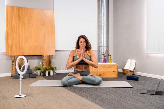Тіло сконцентрованої молодої жінки в активаціях сидить в позі Лотоса з закритими очима і молитовні руки роблять медитацію під час сесії йоги вдома біля смартфона, поміщеного на тринозі. — стокове фото