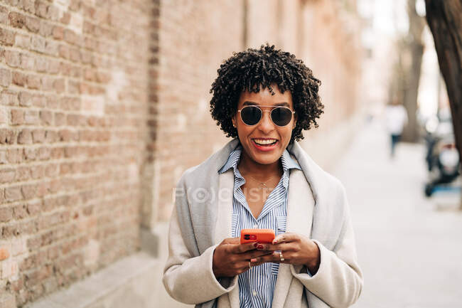 Delighted African American female with curly hair standing near brick wall and browsing mobile phone — Stock Photo