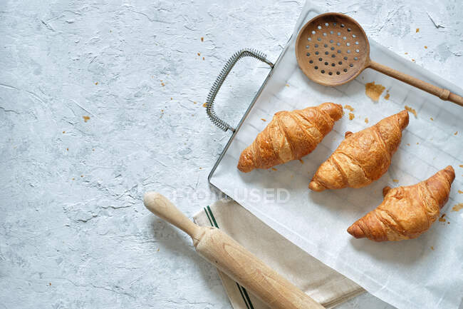 Top view of yummy fresh croissants placed on metal tray on table in kitchen — Stock Photo
