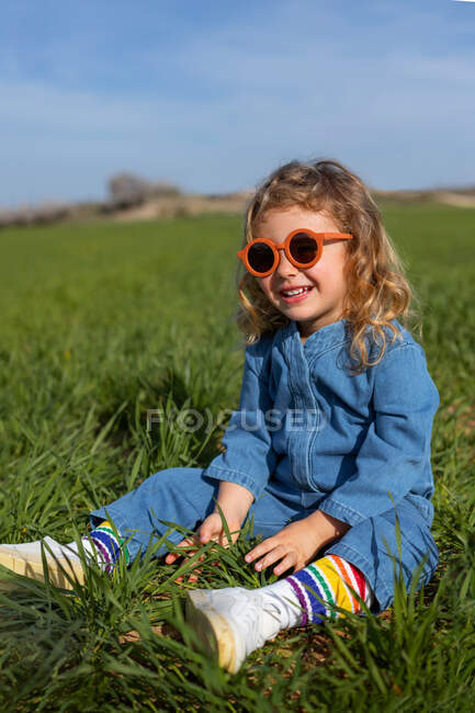Cute happy little girl in trendy clothes and sunglasses sitting and relaxing on grassy lawn — Stock Photo