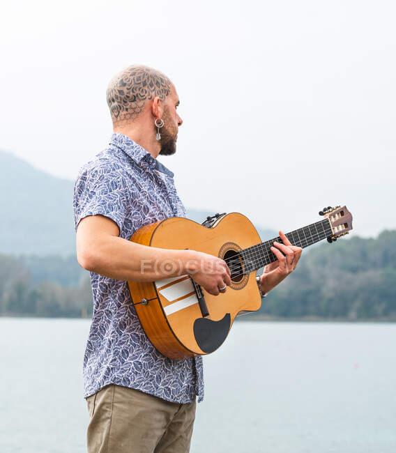 Vista lateral tipo barbudo en ropa casual de pie con la guitarra en el muelle de madera cerca del río con montañas en el fondo bajo el cielo gris nublado en el día - foto de stock