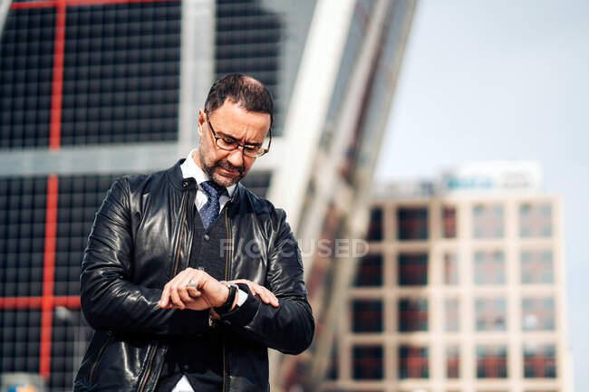 Serious mature Hispanic male executive in formal apparel and eyewear checking time on wristwatch in town — Stock Photo