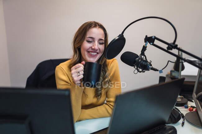 Оптимистичная женщина сидит за столом с компьютерами и пьет горячий напиток, разговаривая с микрофоном во время работы на современной радиостанции — стоковое фото