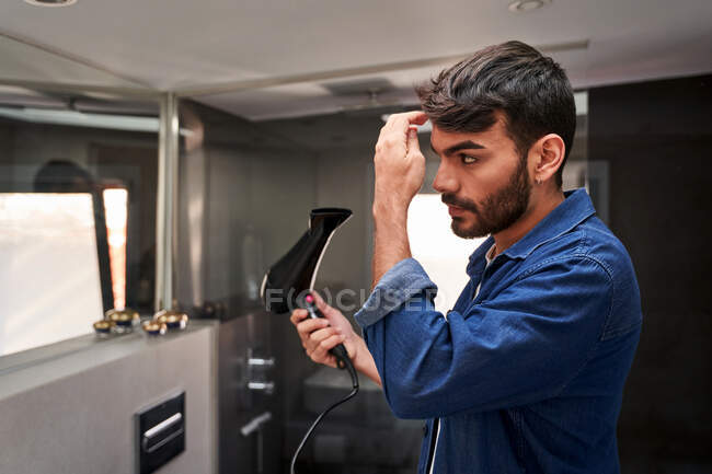 Side view of self assured young bearded Hispanic guy in denim shirt using hairdryer while adjusting hair in bathroom — Stock Photo