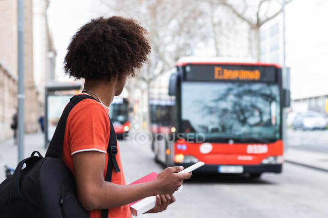 Side view of unrecognizable young African American man in casual clothes and backpack using smartphone while standing on city street and waiting for bus — Stock Photo