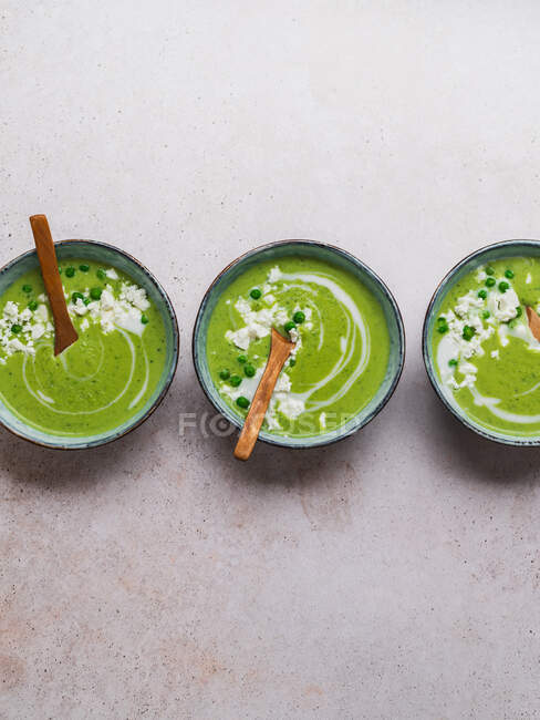 Top view of delicious pea cream soup in bowls served on table — Stock Photo