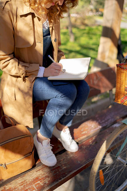 Crop of anonymous young thoughtful female taking notes in planner on wooden bench near bicycle in park in daytime — Stock Photo