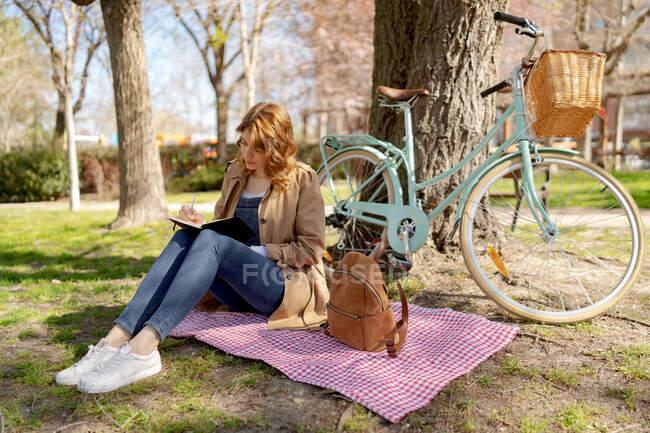Cuerpo completo de hembra joven concentrada tomando notas en cuaderno sobre tela a cuadros con mochila cerca de la bicicleta en el parque - foto de stock