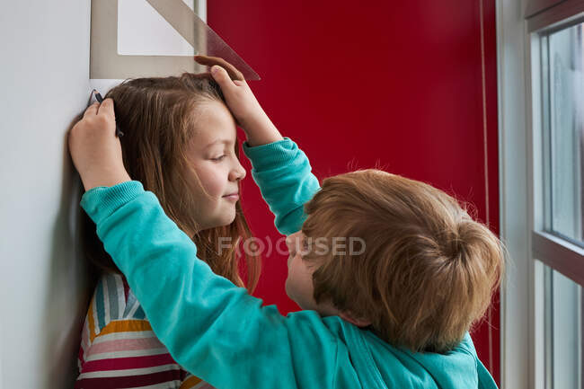 Brother helping sister with measuring her height with ruler and pencil near wall — Stock Photo