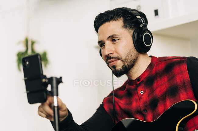 Tripod with camera placed near man playing guitar in house room — Stock Photo