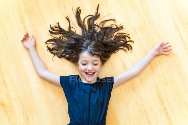 Vue du dessus ravi petite fille avec les yeux fermés couché sur le parquet avec les cheveux et les bras tendus et riant joyeusement — Photo de stock
