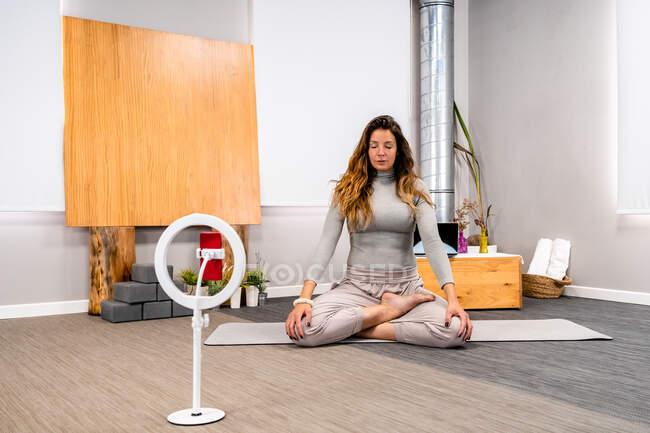 Тіло сконцентрованої молодої жінки в активаціях сидить в позі Лотоса з закритими очима, медитуючи під час сеансу йоги вдома біля смартфона, поміщеного на тринозі. — стокове фото