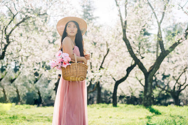 From below side view of female in dress and straw hat standing with basket in blooming garden looking away — Stock Photo