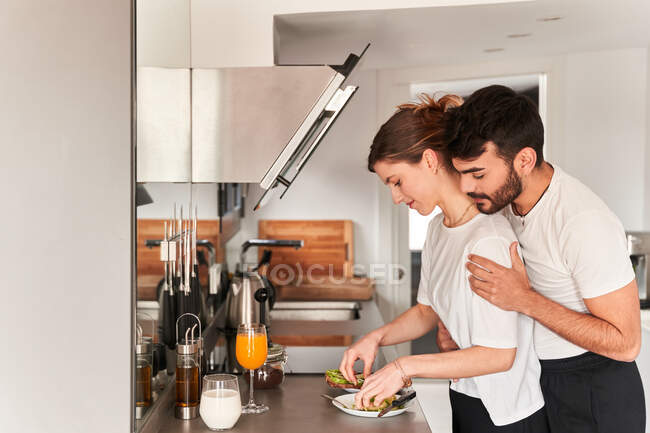 Side view of young romantic ethnic guy in white t shirt smiling and hugging happy girlfriend preparing healthy breakfast with avocado in kitchen — Stock Photo