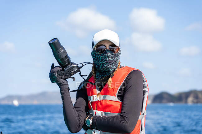 Front view of anonymous female traveler in life jacket and scarf with professional camera during trip — Stock Photo