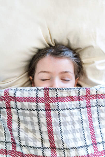 Top view serene cute girl sleeping peacefully on cozy pillow and covering half face with comfortable blanket in daylight — Stock Photo