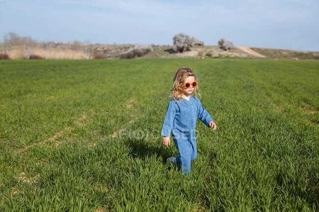Menina feliz bonito em roupas da moda e óculos de sol de pé e relaxante no gramado gramado — Fotografia de Stock