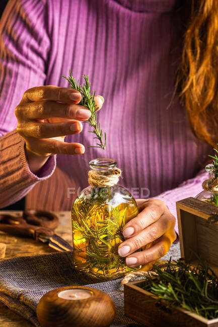 Crop faceless female in purple sweater putting herbs twigs with green leaves in essential oil glass bottle near scissors and rope with small chest on cloth at wooden table — Stock Photo