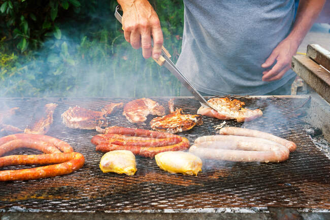 Crop anonymous male cook preparing delicious pork steaks with different sausages and chicken breasts on grill grate with smoke — Stock Photo