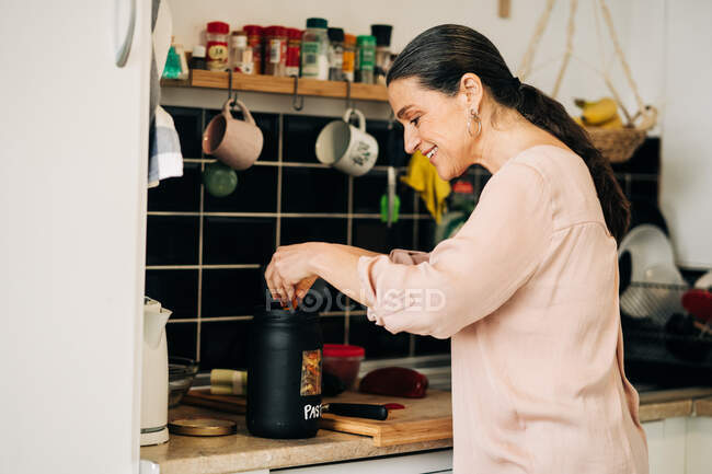 Side view of positive middle aged putting cut vegetables into container while cooking lunch at kitchen counter with cutting board and dishware — Stock Photo