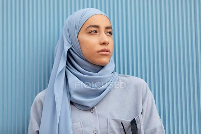 Giovane donna musulmana solitaria con sguardo malinconico che guarda lontano contro la parete a costine durante il giorno — Foto stock