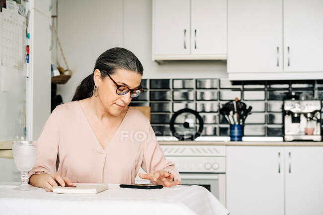 Concentrated middle aged female in eyeglasses surfing cellphone while sitting at table with notebook in modern kitchen with kitchenware at home — Stock Photo