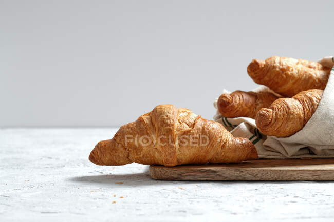 Freshly baked croissants served on wooden cutting board with napkin on table for breakfast — Stock Photo