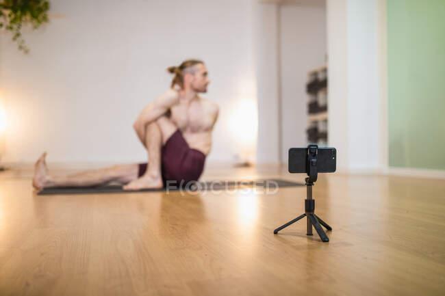 Foco suave do smartphone no tripé gravação sessão de ioga do treinador praticando Marichyasana no tapete esportivo em estúdio — Fotografia de Stock