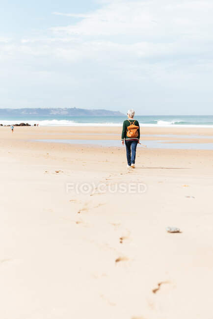 Back view of unrecognizable senior female trekker walking on sandy shore against endless sea during trip — Stock Photo