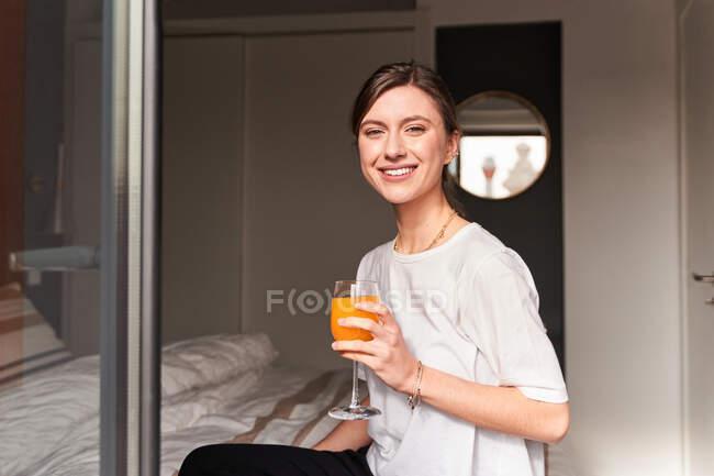Conteúdo jovem fêmea em roupas casuais sorrindo e bebendo suco fresco sentado na cama confortável perto da janela enquanto olha para a câmera — Fotografia de Stock