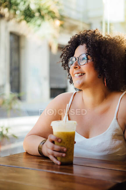 Adult cheerful female in eyewear sitting at urban cafeteria table with glass of beverage while looking away — Stock Photo