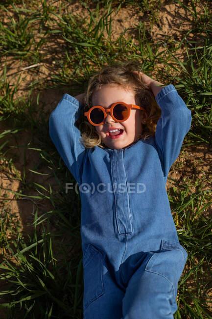 De arriba chica en ropa de moda y gafas de sol de la mano detrás de la cabeza y relajarse en el césped cubierto de hierba - foto de stock
