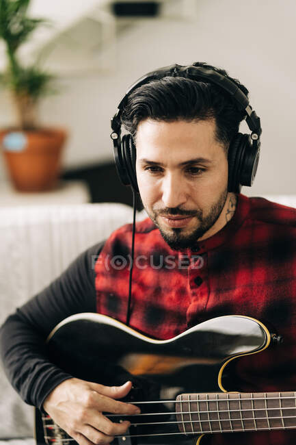 Adult male musician in headphones playing bass guitar against netbook on sofa in living room — Stock Photo