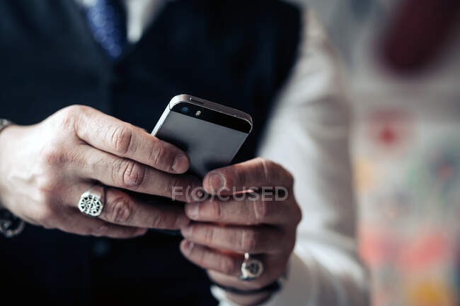 Crop unrecognizable male executive in rings text messaging on mobile phone on blurred background — Stock Photo