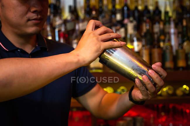Бармен працює з шейкером для змішування коктейлю в барі. — стокове фото