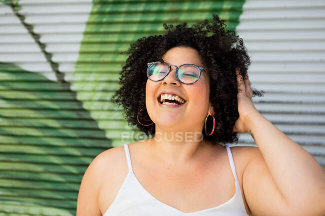 Content adult overweight female in eyewear touching curly hair against ornamental wall in daytime — Stock Photo