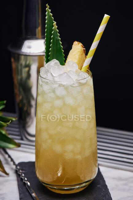 Coquetel amarelo em vidro decorado com pedaço de abacaxi e folhas verdes com palha de papel colocada na montanha-russa com colher de bar — Fotografia de Stock