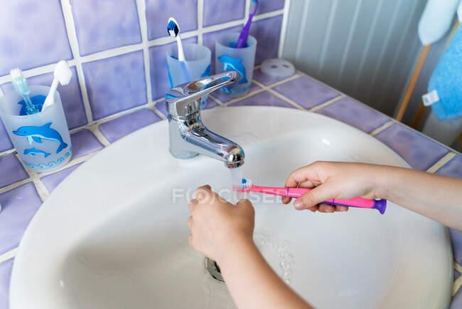 De cima anônimo menina lavar a escova de dentes no banheiro — Fotografia de Stock