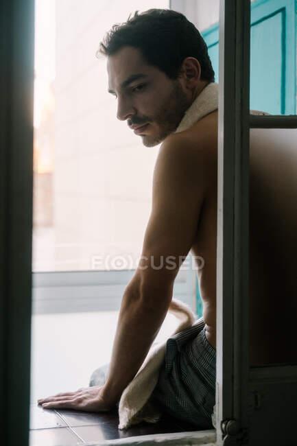 Homem calmo e sem camisa com barba apoiada na janela em casa e olhando para trás — Fotografia de Stock