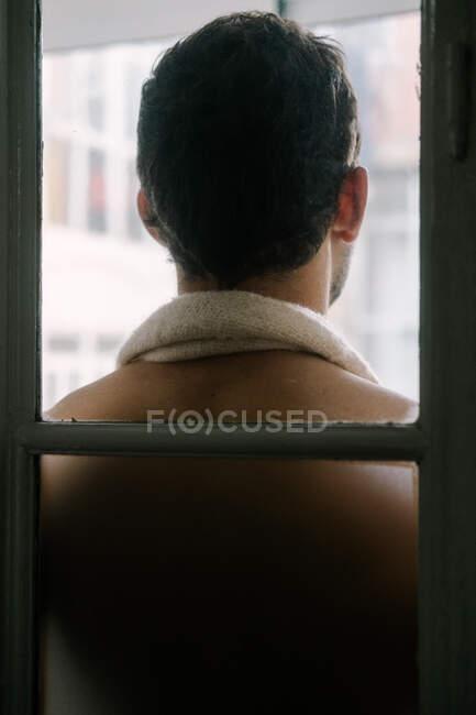Visão traseira do macho com torso nu em pé perto da janela em casa e olhando para longe — Fotografia de Stock