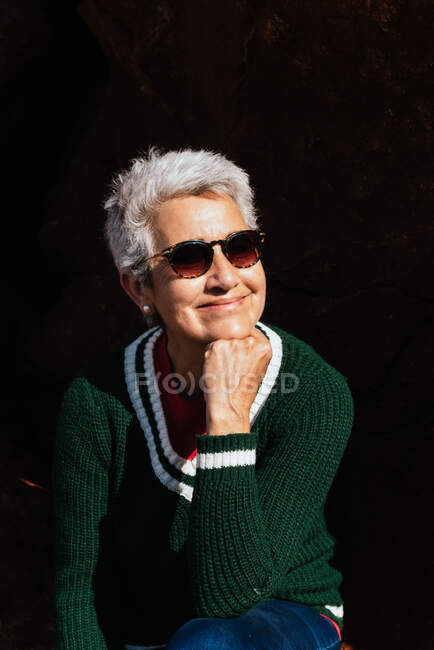 Cheerful elderly female in knitted sweater with gray hair leaning on hand on sunny day — Stock Photo