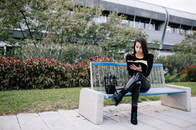 Stylish female entrepreneur sitting on bench and taking notes in organizer while working in urban park — Stock Photo