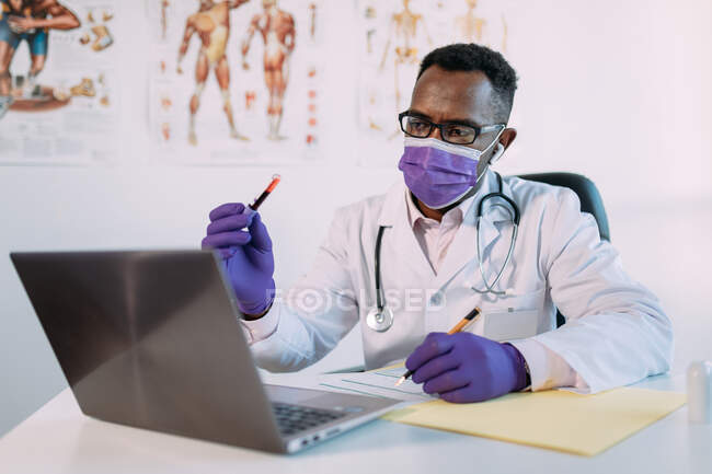 Unrecognizable serious black male scientist in medical robe and mask demonstrating blood sample in test tube while having video call on laptop in clinic — Stock Photo