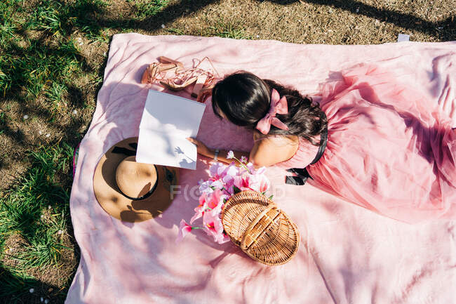 High angle of unrecognizable female in stylish dress lying on blanket with flowers in wicker basket and shoes with straw hat and reading book in garden — Stock Photo