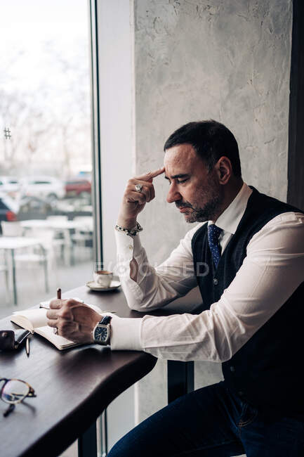 Side view of pensive mature Hispanic male entrepreneur touching forehead at table with agenda in cafeteria — Stock Photo